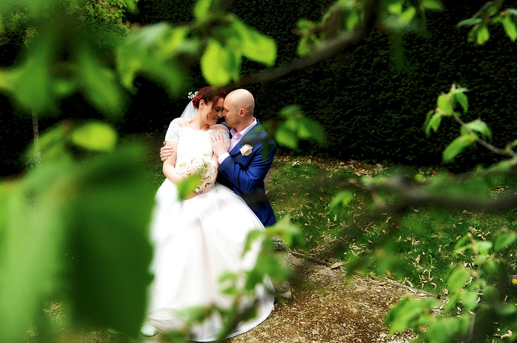 Intimate wedding photograph from Surrey wedding venue Leatherhead Register Office taken discreetly through some greenery of newlyweds sharing a moment