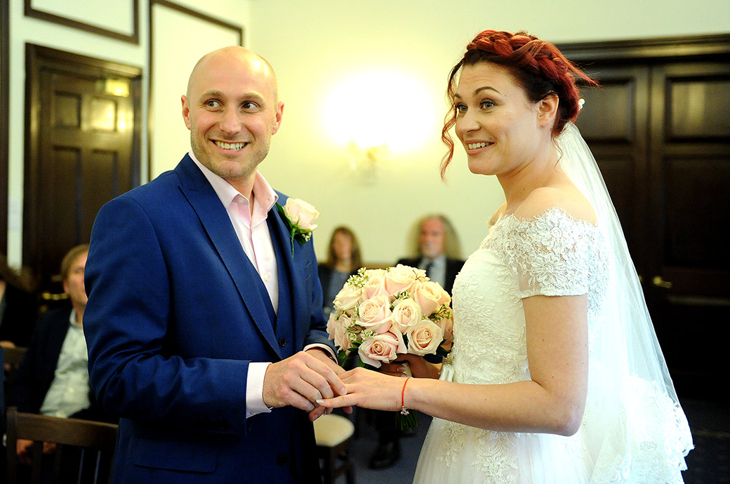 The smiling and excited Bride and Groom look towards the marriage registrar during the wedding ceremony in the State Room at Leatherhead Registry Office Surrey