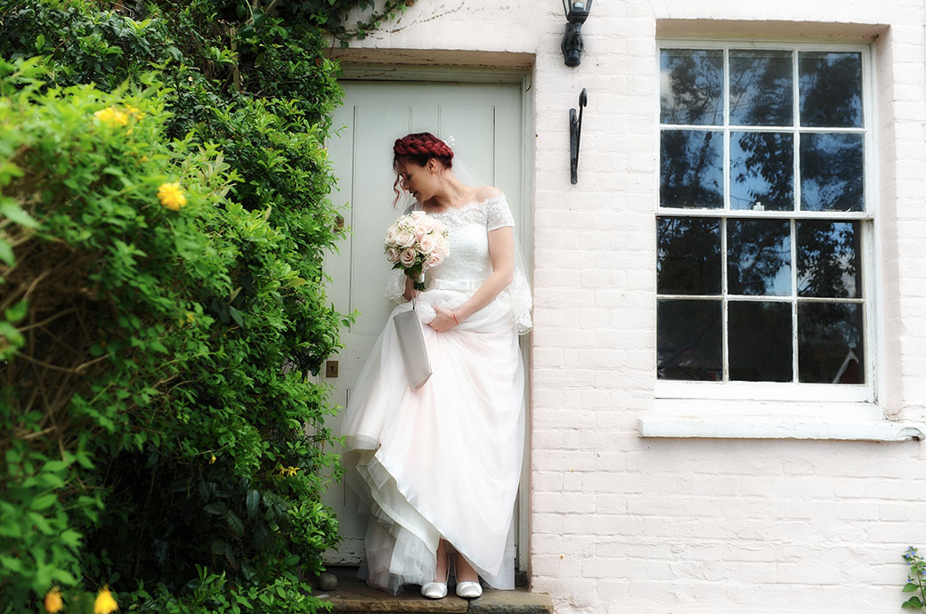 Bride with wedding bouquet in hand leaves the door of her house ready to get to popular Surrey wedding venue Leatherhead Register Office
