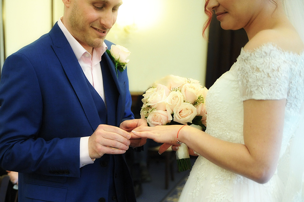 Close up wedding photograph taken at Surrey wedding venue Leatherhead Registry Office of the Groom carefully pushing the wedding ring onto his Bride's finger