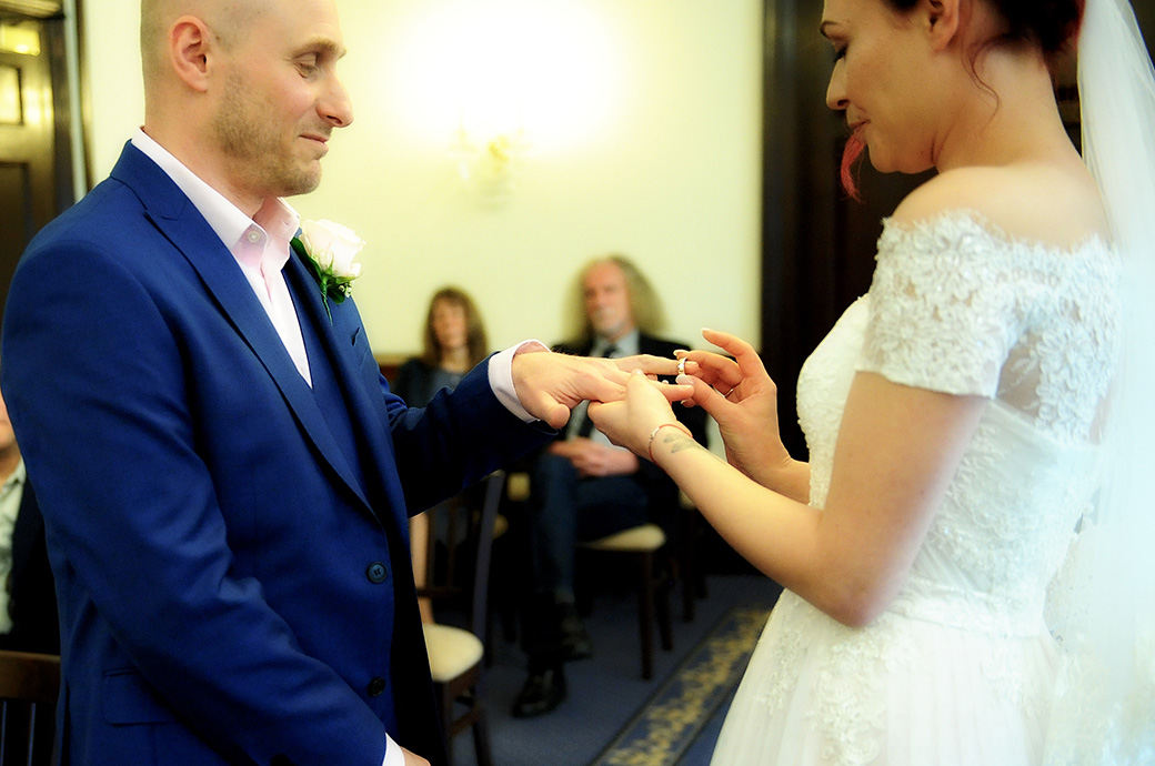 The groom smiles in the State Room at Leatherhead Register Office Surrey as his Bride gently pushes the wedding ring onto his finger