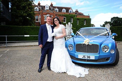 Just married couple standing in front of their Blue Bentley outside the fascinating Surrey wedding venue Littleton Park House at the famous Shepperton Studios