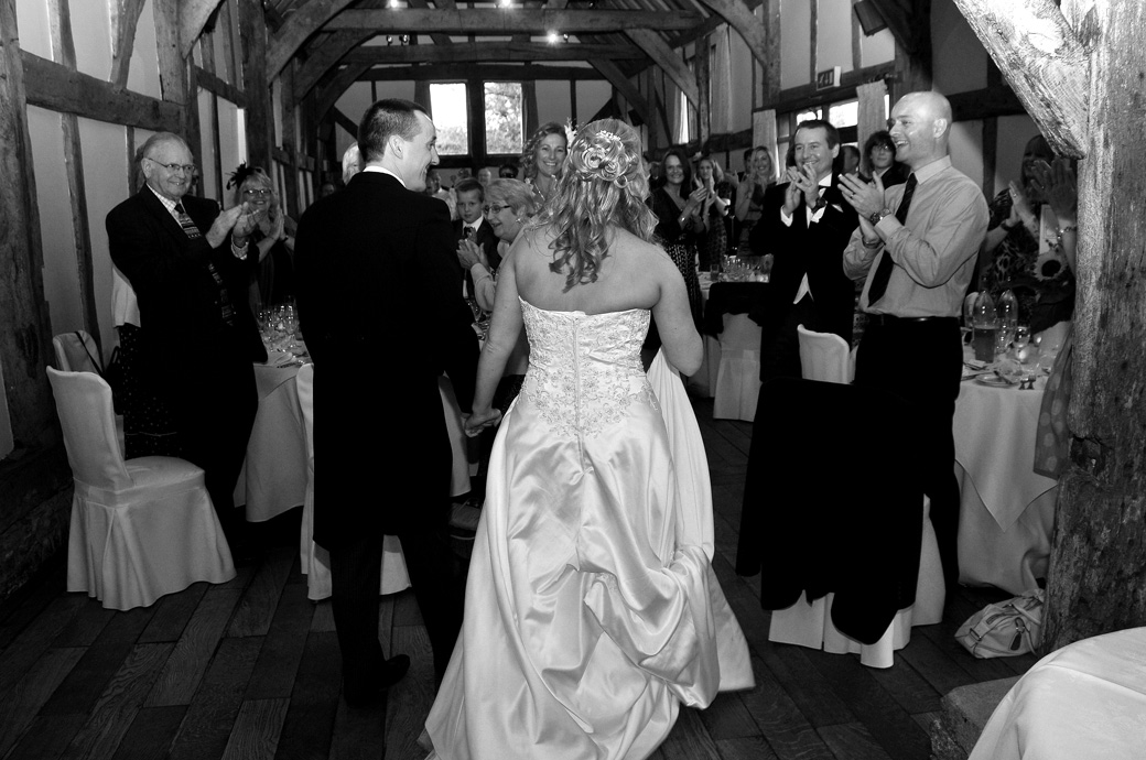 Bride and Groom entering the Tithe Barn for dinner as everyone applauds in this all smiles wedding photo taken at Surrey wedding venue Loseley Park