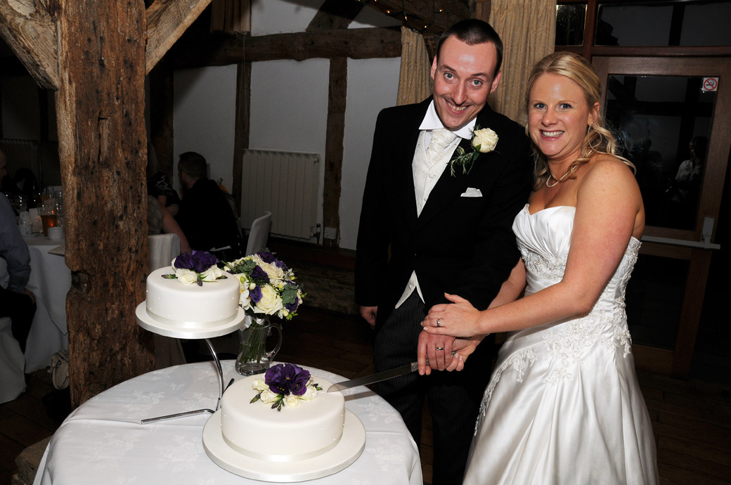 A beaming happy couple cutting their cake wedding picture captured at the grand and historic Loseley Park in Surrey during the reception in the 17th Tithe Barn