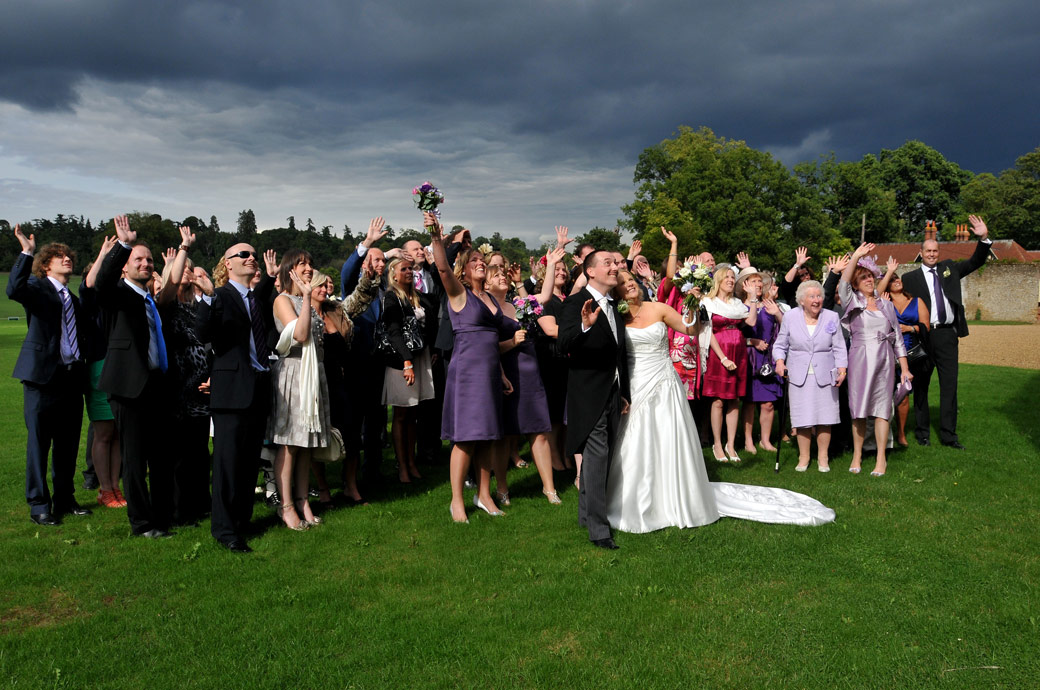 Everyone on the lawn waving in front of a dramatic sky wedding picture taken as they pose for the Surrey wedding photographer at Loseley Park who's leaning out of the upstairs window