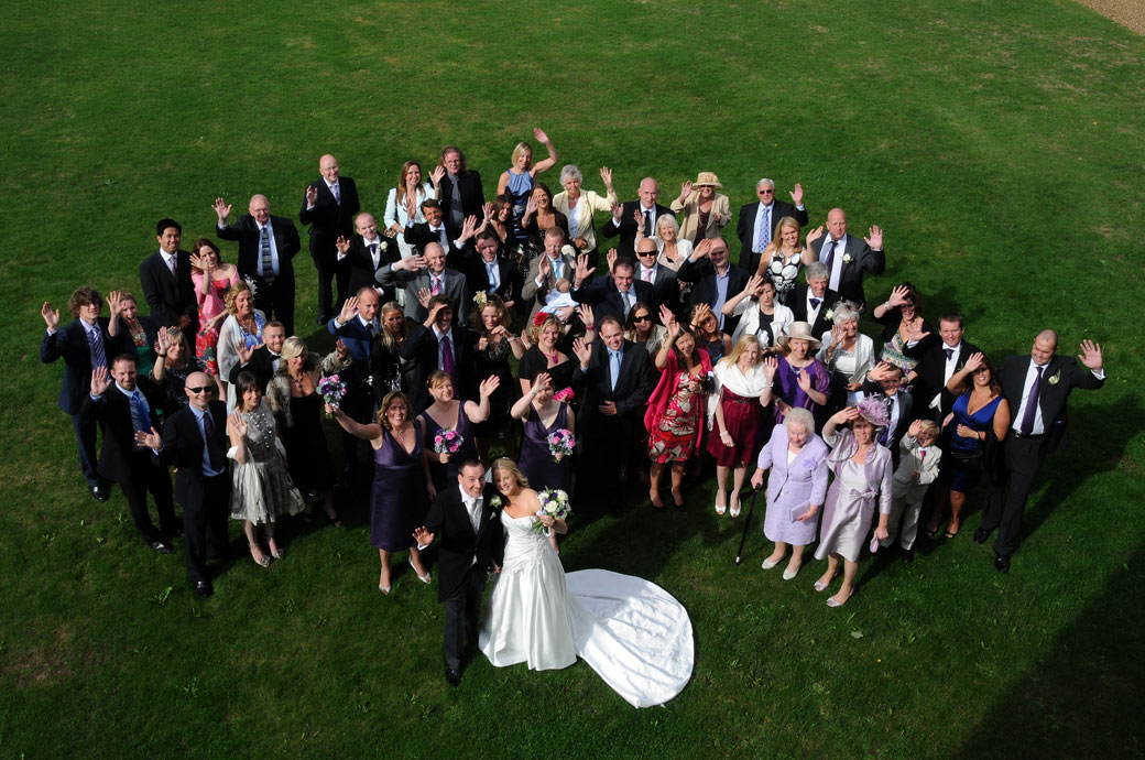 Everybody on the lawn waving wedding photo taken from the first floor of the wonderful 14th Century Surrey wedding venue Loseley Park in Guildford