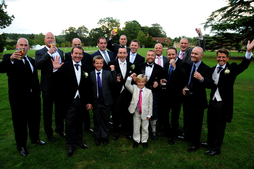 The gents say cheers with their drinks raised in this fun wedding photo taken on the lawn outside the Tithe Barn at the beautiful Loseley Park by Surrey Lane wedding photography