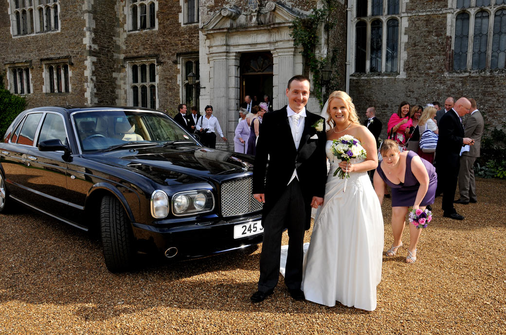An happy couple standing by their Bentley in this wedding photo taken on the gravel drive outside Loseley Park in Surrey a magnificent 14th Century Elizabethan mansion