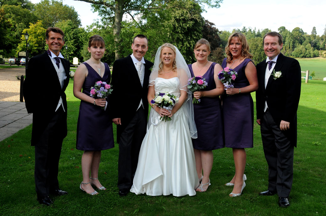 An all smiles group wedding photograph taken at the wonderful Surrey wedding venue Loseley Park outside the 17th Century Tithe Barn on the lawn reception