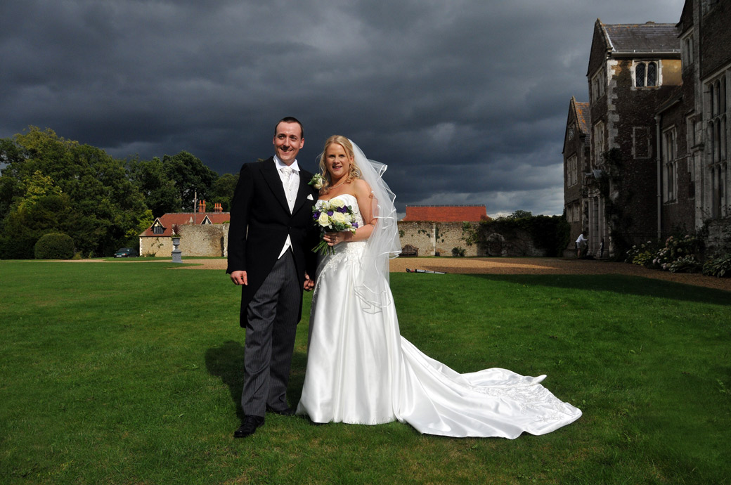 Bride and Groom standing on the lawn in front of a dramatic grey blue sky wedding photo captured at Loseley Park by Surrey Lane wedding photography