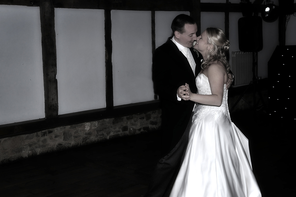Loving Bride and Groom taking the first dance in this wedding picture captured in the 17th Century Tithe Barn at Loseley Park Guildford Surrey