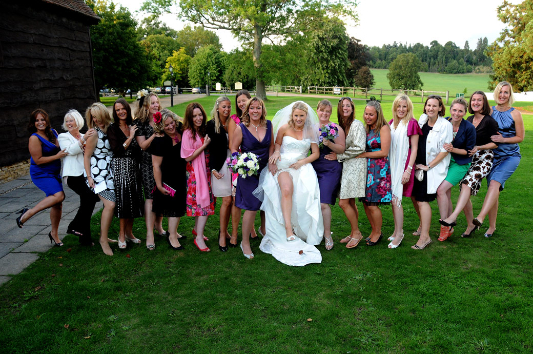 Bride and her ladies all shaking a leg in this fun group wedding picture taken on the lawn outside the the Tithe Barn at the stunning wedding venue Loseley Park in Guildford Surrey
