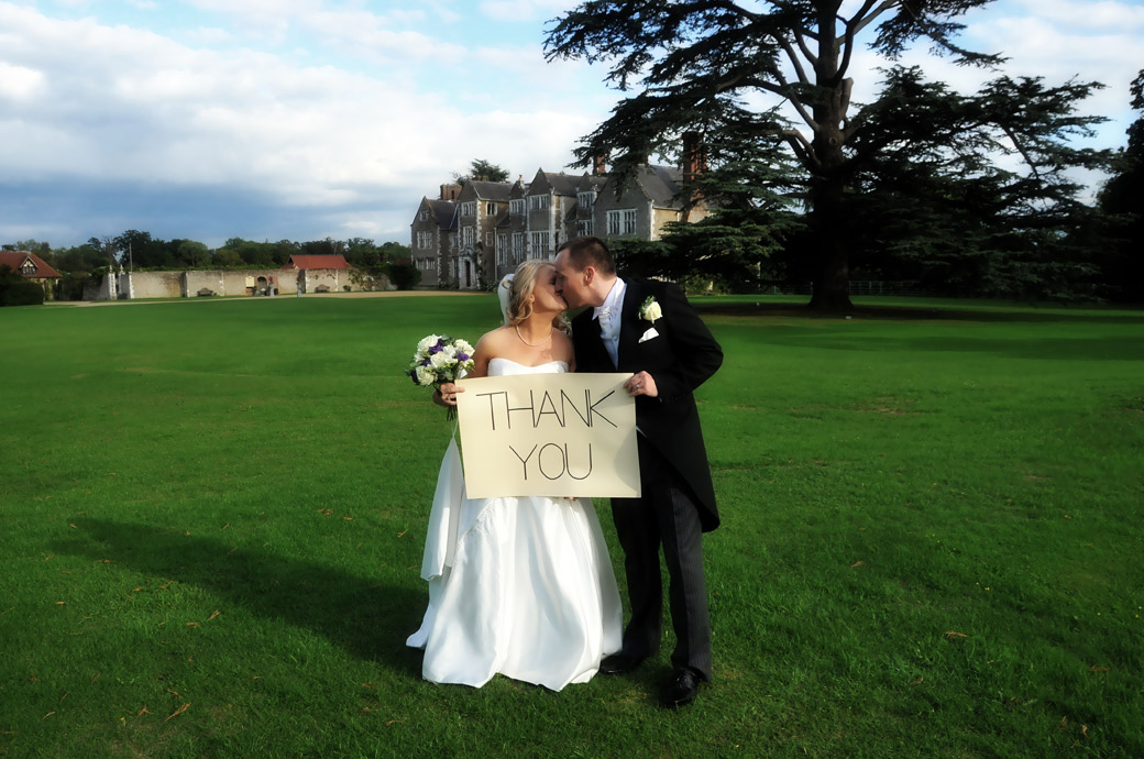 Newly-weds having a romantic kiss on lawn wedding photograph as they hold a thank you notice up captured at the beautiful Loseley Park a wonderful Surrey wedding venue