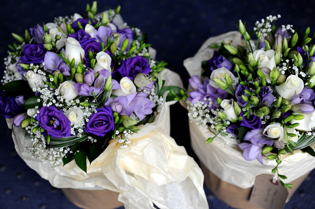 Beautiful bouquets of purple mauve and white flowers waiting in jars of water captured at Lythe Hill Hotel Haslemere by a Surrey Lane wedding photographer
