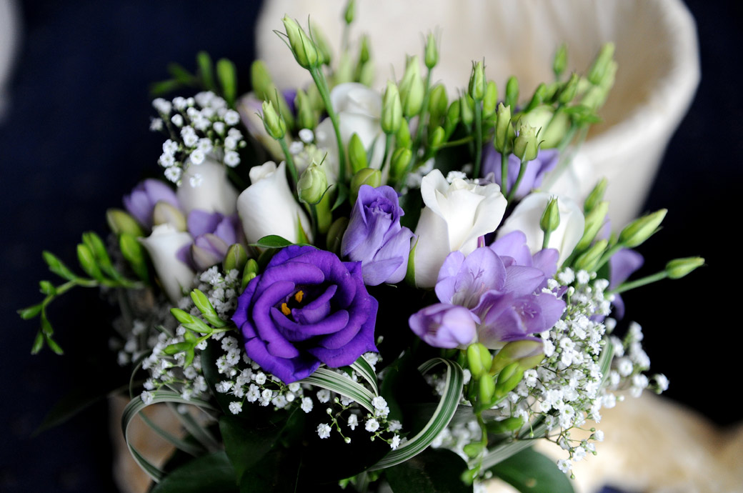 Bride's beautiful wedding bouquet of purple mauve and white flowers ready to picked up for the marriage ceremony at Lythe Hill Hotel a popular Surrey wedding venue