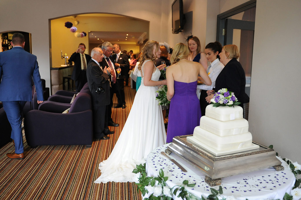 Beyond the wedding cake the Bride talking to guests over canapés as everyone relaxes in the lounge bar area after the marriage ceremony at Lythe Hill Hotel Haslemere Surrey