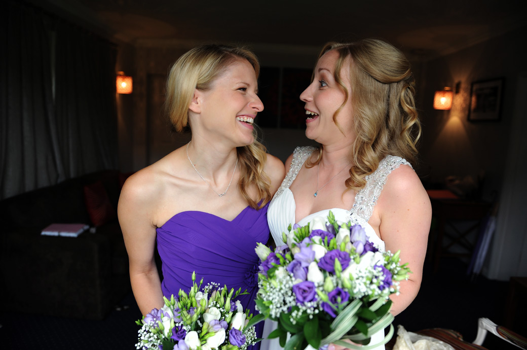 Bride and Bridesmaid share some fun together before leaving the Tennyson Room for the wedding ceremony in the Garden Room at  Lythe Hill Hotel Haslemere