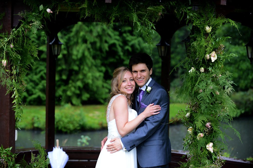 A delighted smiling and happy couple have a hug as they celebrate their marriage in the gazebo out of the rain at Surrey wedding venue Lythe Hill Hotel in Haslemere