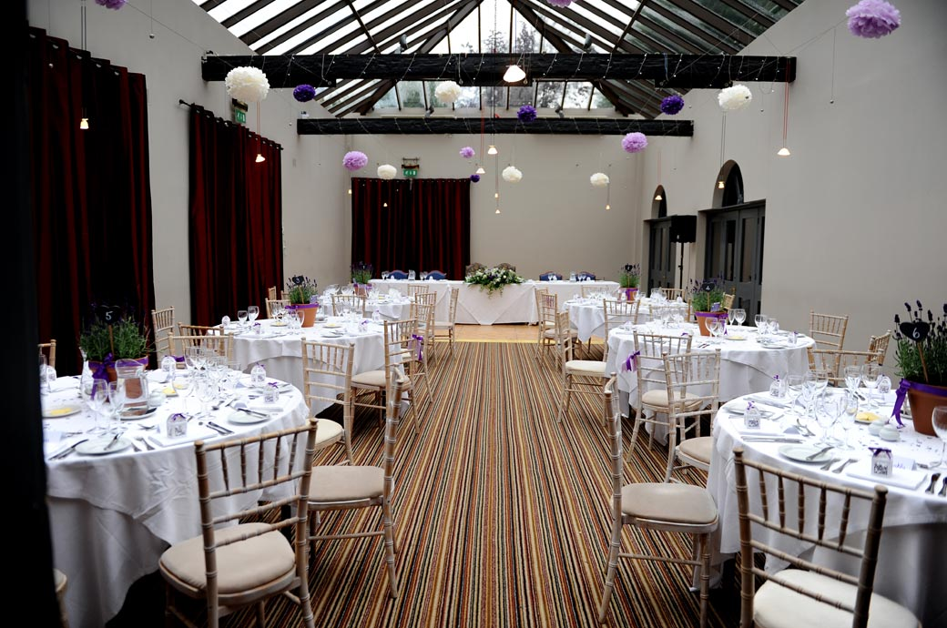 The Garden Room captured in this wedding photo dressed and ready for the wedding breakfast at Surrey wedding venue Lythe Hill Hotel in green and leafy Haslemere