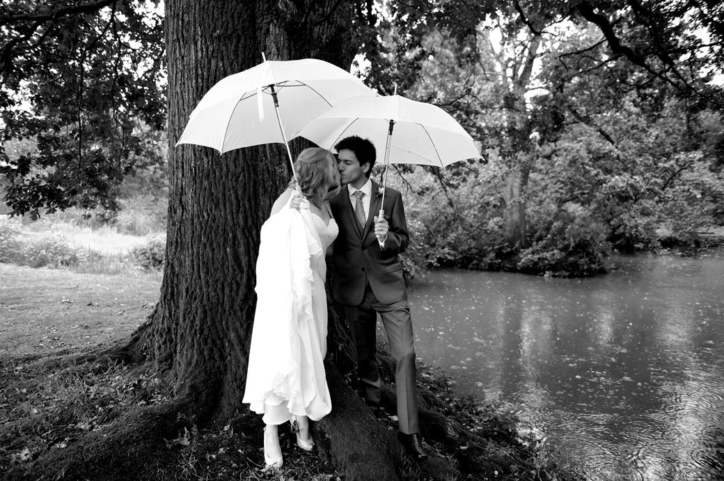Newlyweds captured in this romantic wedding photograph taken at Surrey wedding venue Lythe Hill Hotel as they kiss  under umbrellas by a tree and lake in the pouring rain