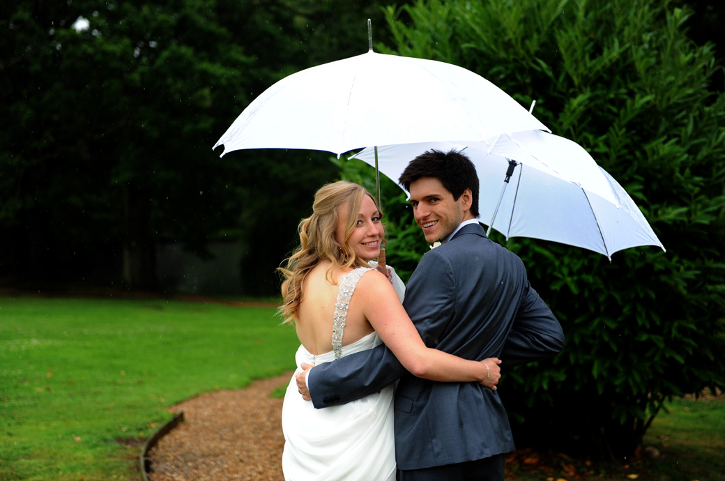Relaxed smiling newlywed couple look back over the shoulders under their white umbrellas in the lovely green grounds of Surrey wedding venue Lythe Hill Hotel in heavy rain