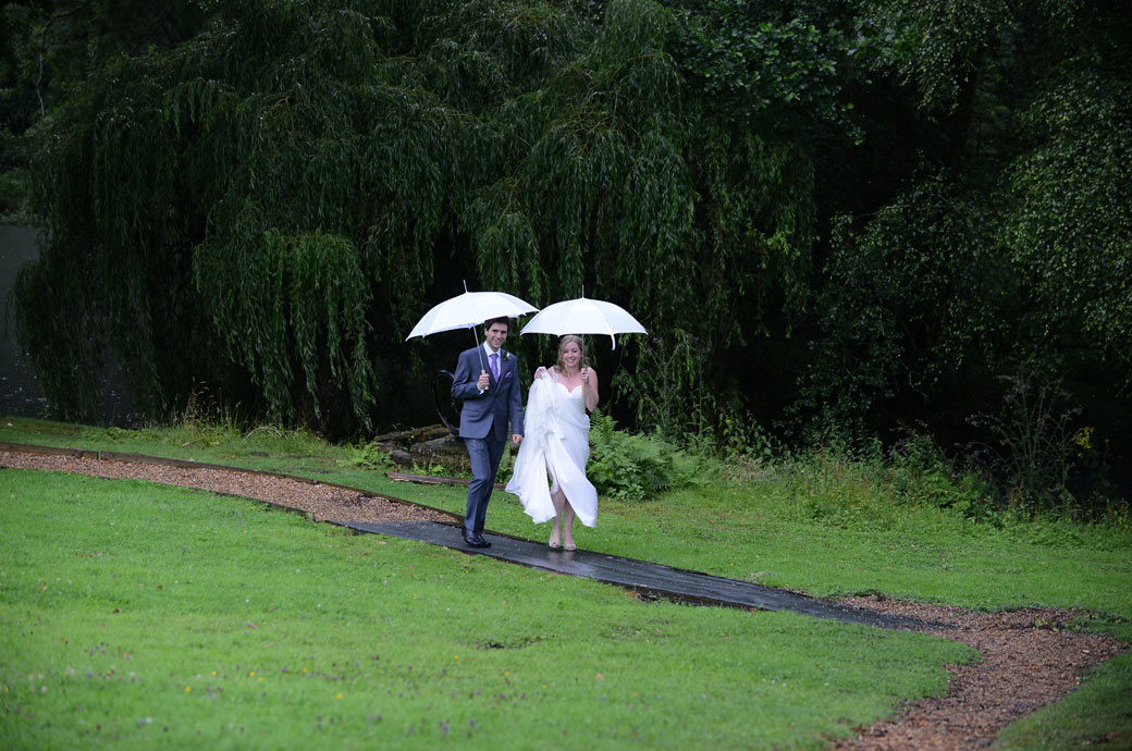 Bride and Groom walking along the path through the tress in the rain with white umbrellas taken in the grounds of Surrey wedding venue Lythe Hill Hotel in Haslemere