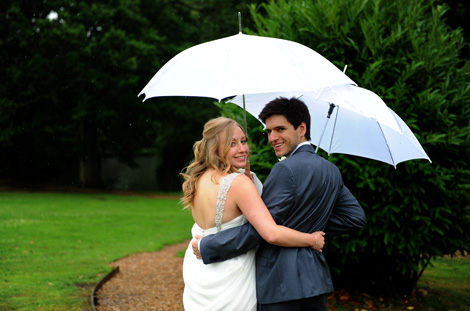 Smiling newlyweds in lovely wedding photograph taken arm in arm under a white umbrella after getting married at Surrey wedding venue Lythe Hill Hotel in Haslemere