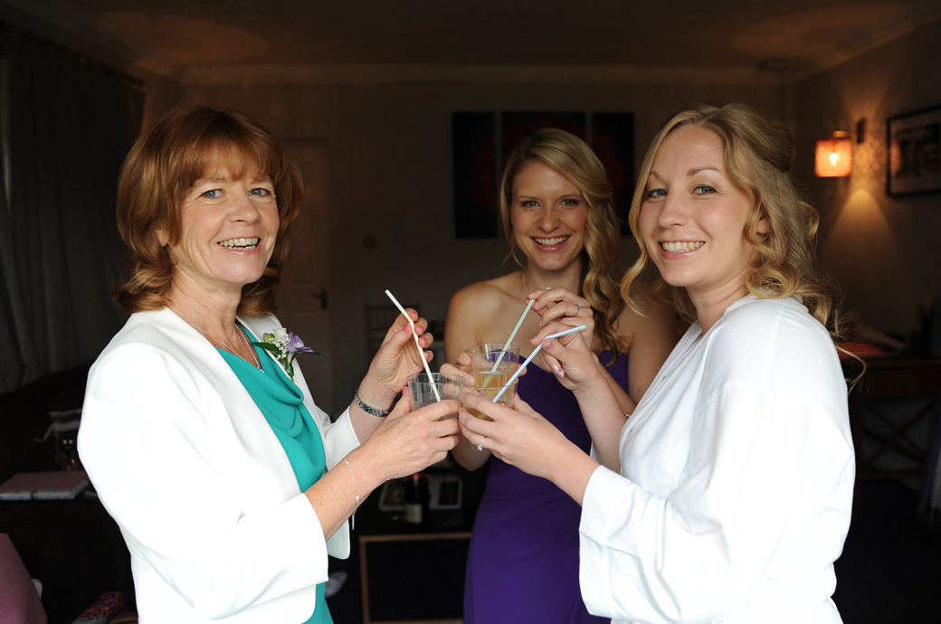 Wedding photo of smiling Bride with mother and bridesmaid as they sip champagne with straws at Surrey wedding venue Lythe Hill Hotel in the Tennyson Room