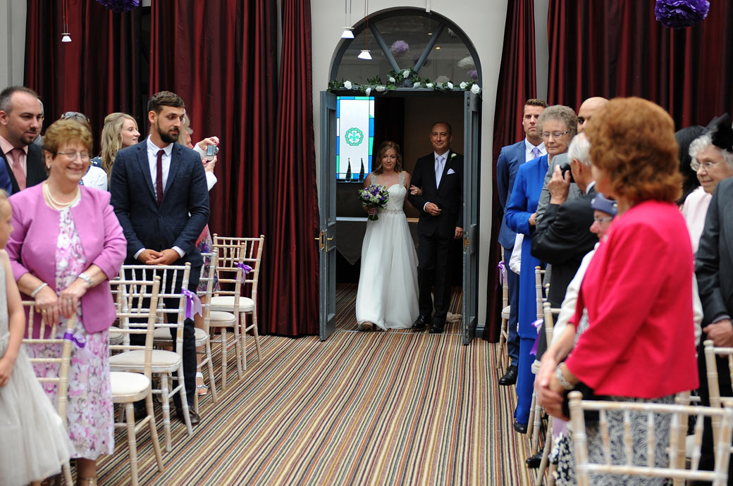 Bride enters the  Garden Room on her father's arm and starts the walk down the aisle to get married at Surrey wedding venue Lythe Hill Hotel in leafy Haslemere