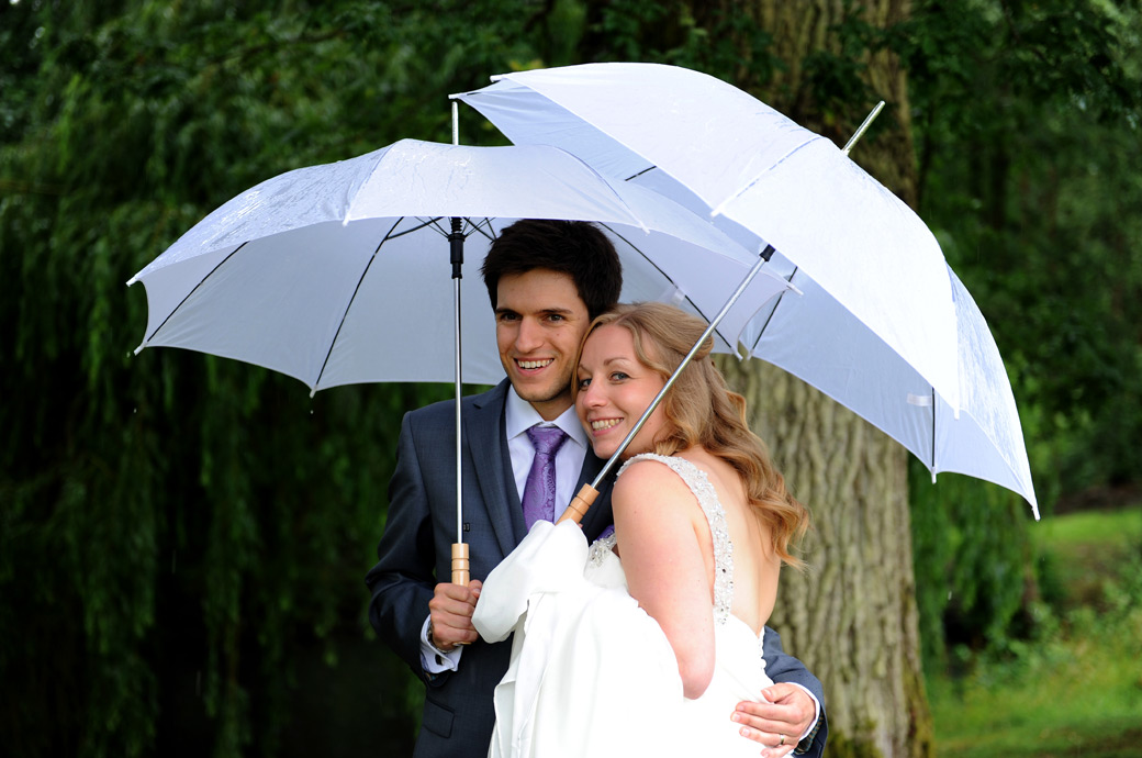 Beautiful happy Bride standing with her smiling Groom under the protection of their white umbrellas on a raining wedding day at Lythe Hill Hotel in Surrey