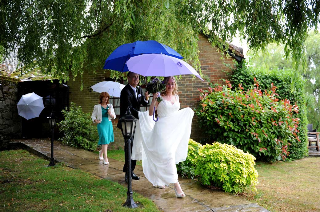 Bride elegantly walking from the Tennyson Room in the rain helped by dad and followed by mum at Surrey wedding venue Lythe Hill Hotel all under umbrellas