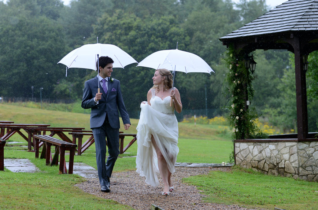 Beautiful romantic wedding photo of the Bride hitching up her wedding dress as she walks in the rain with the Groom at Lythe Hill Hotel a beautiful Surrey wedding venue in Haslemere