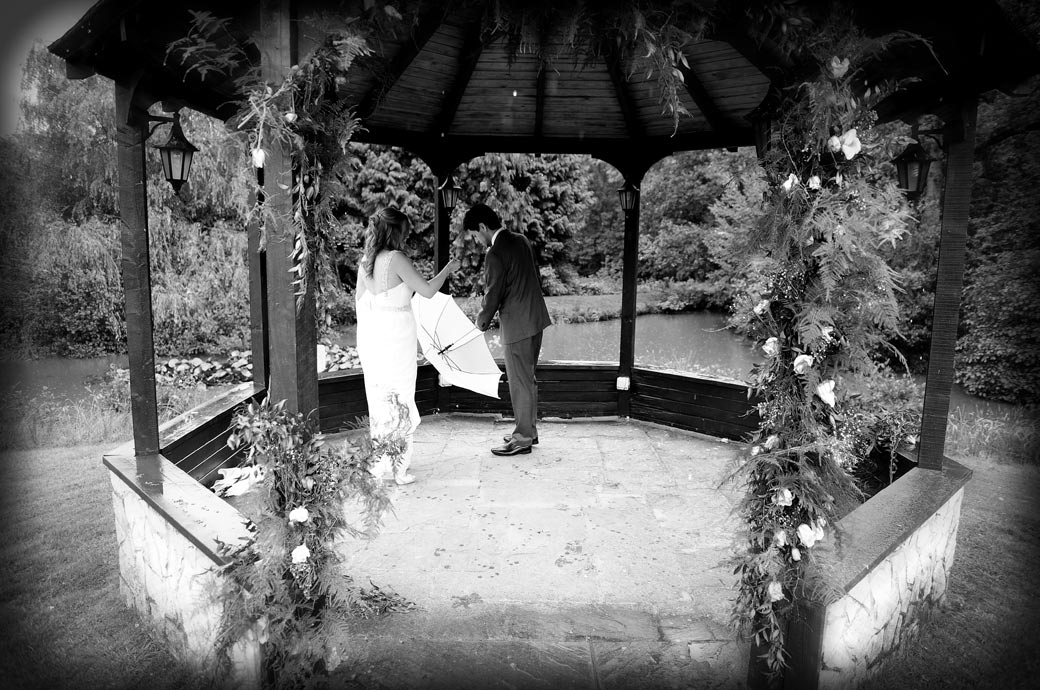 Bride and groom captured by a Surrey Lane wedding photographer as they stop under cover and shake their umbrellas at the Lythe Hill Hotel in the picturesque Gazebo