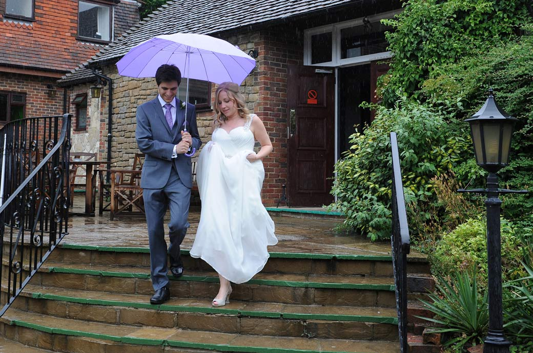 Newlyweds carefully walking done the wet steps under a white room from the Garden Room as they head for the lawn at Lythe Hill Hotel in Haslemere Surrey