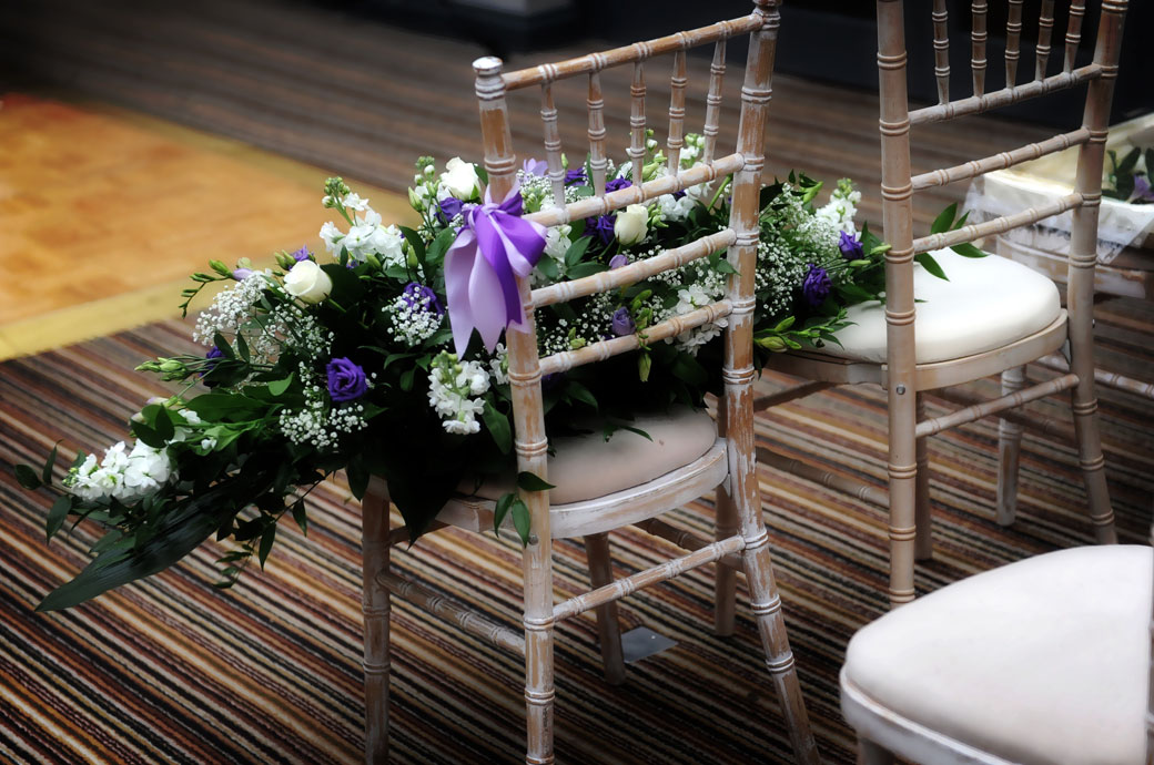 Wedding flower display sitting on a chair awaiting pick up in this picture taken in the Garden Room prior to a marriage ceremony at Surrey wedding venue Lythe Hill Hotel