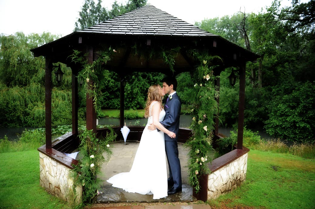 Standing at the entrance to the gazebo at Surrey wedding venue Lythe Hill Hotel wedding photograph of the newlywed couple under cover from the rain having a romantic kiss