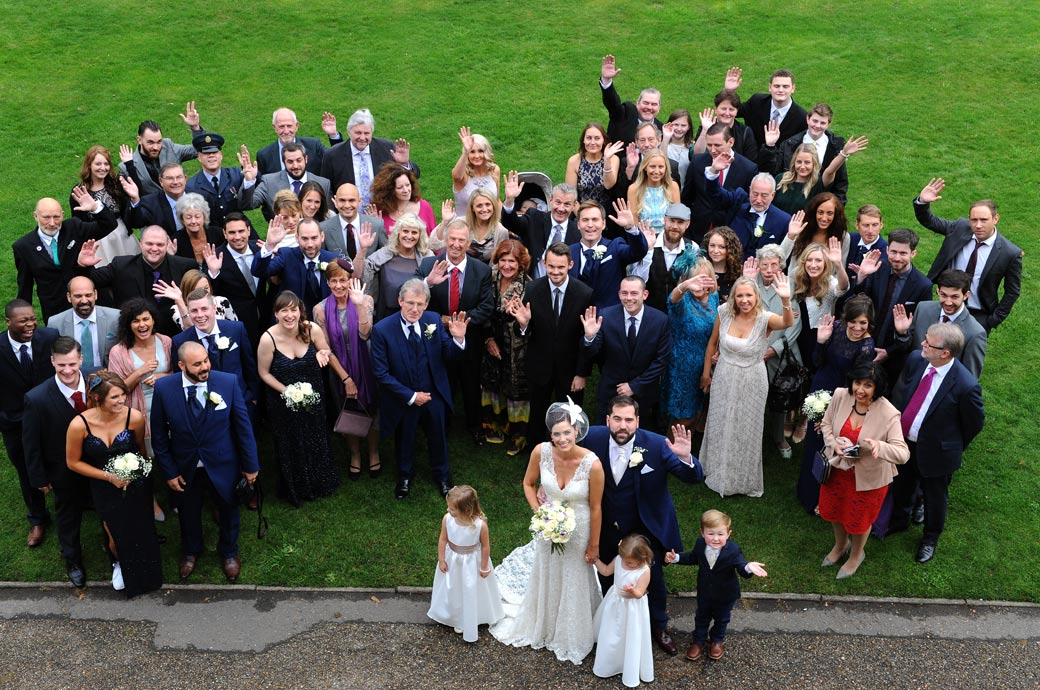 Wedding photograph taken from a top floor of Surrey wedding venue Nonsuch Mansion in Cheam of the Bride and Groom with all their guests waving for the everyone group photo