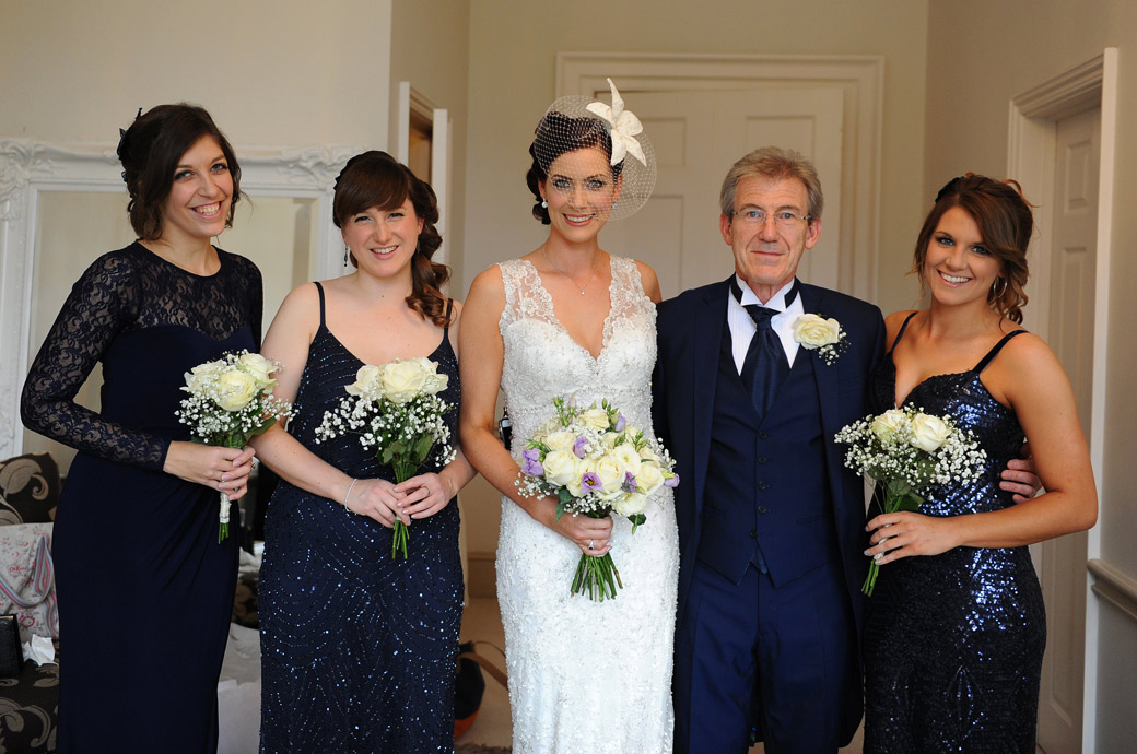 Beautiful bride with her father and bridesmaids ready to leave the bridal suite at Nonsuch Mansion in Surrey to have her interview with the marriage registrars