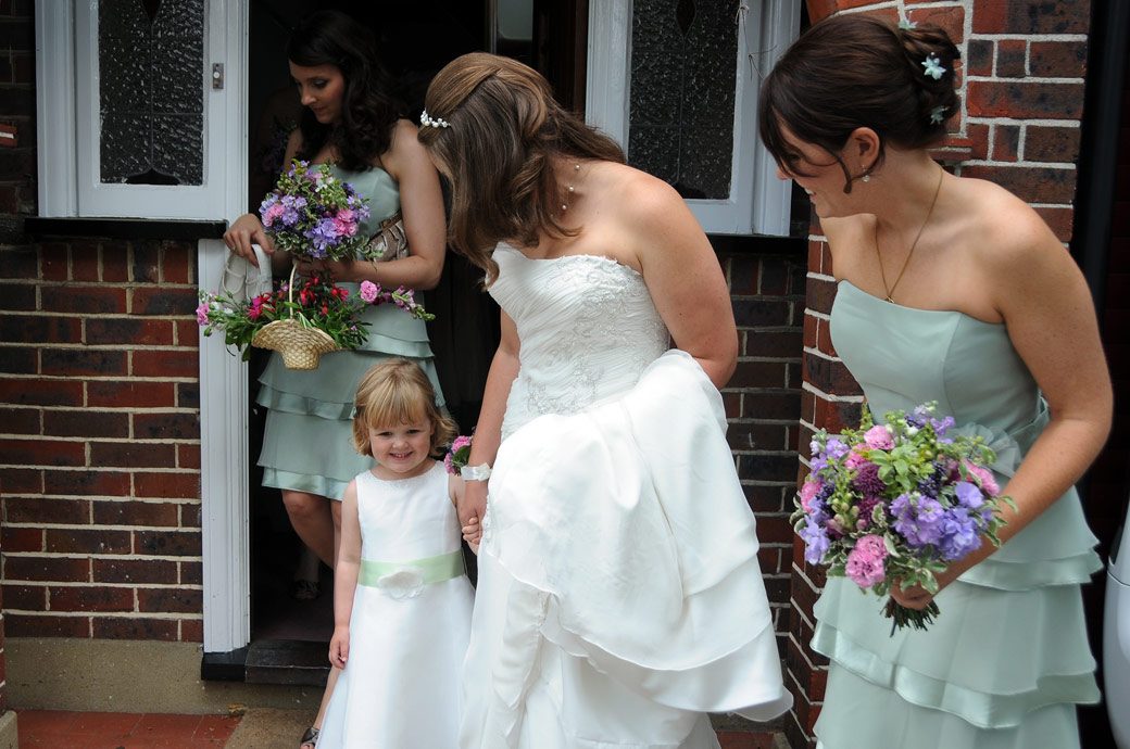 A smiling flower girl is helped by the Bride as they leave the house on their way to the wedding in Cheam Surrey at the lovely eye catching Nonsuch Mansion