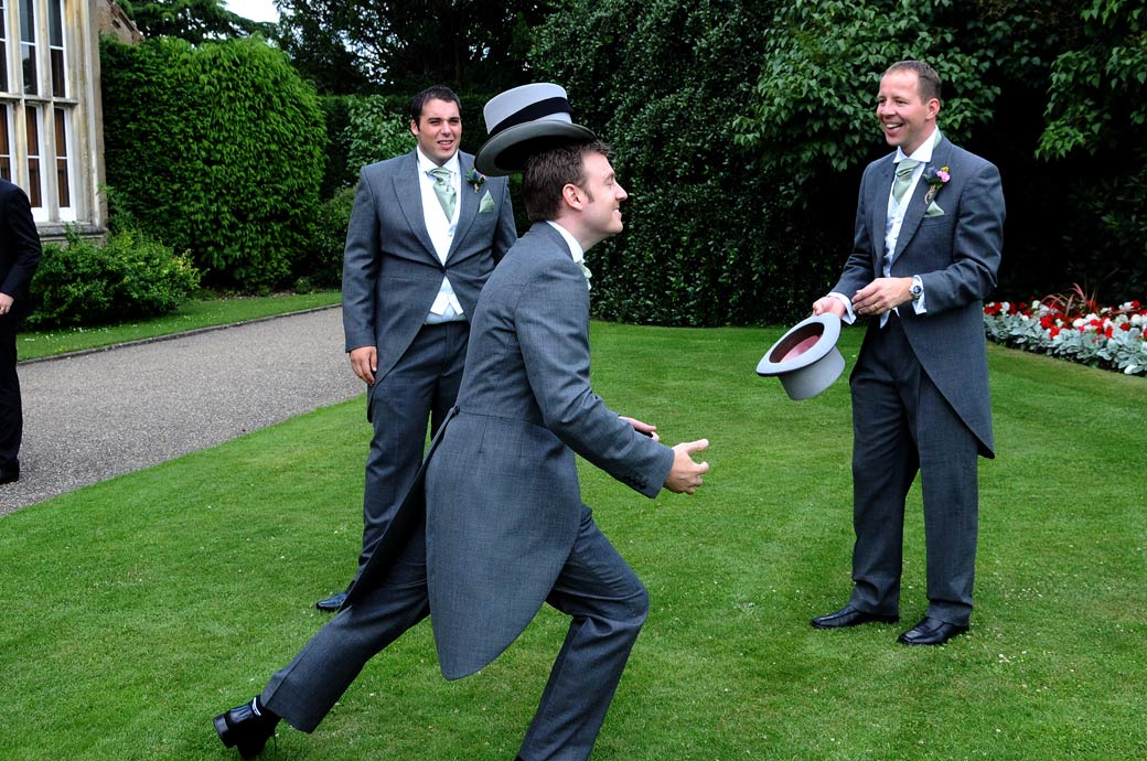 Funny wedding picture of a Groomsmen trying to catch a top hat on his head out on the lawn at  Nonsuch Mansion in Cheam captured by a Surrey Lane wedding photographer