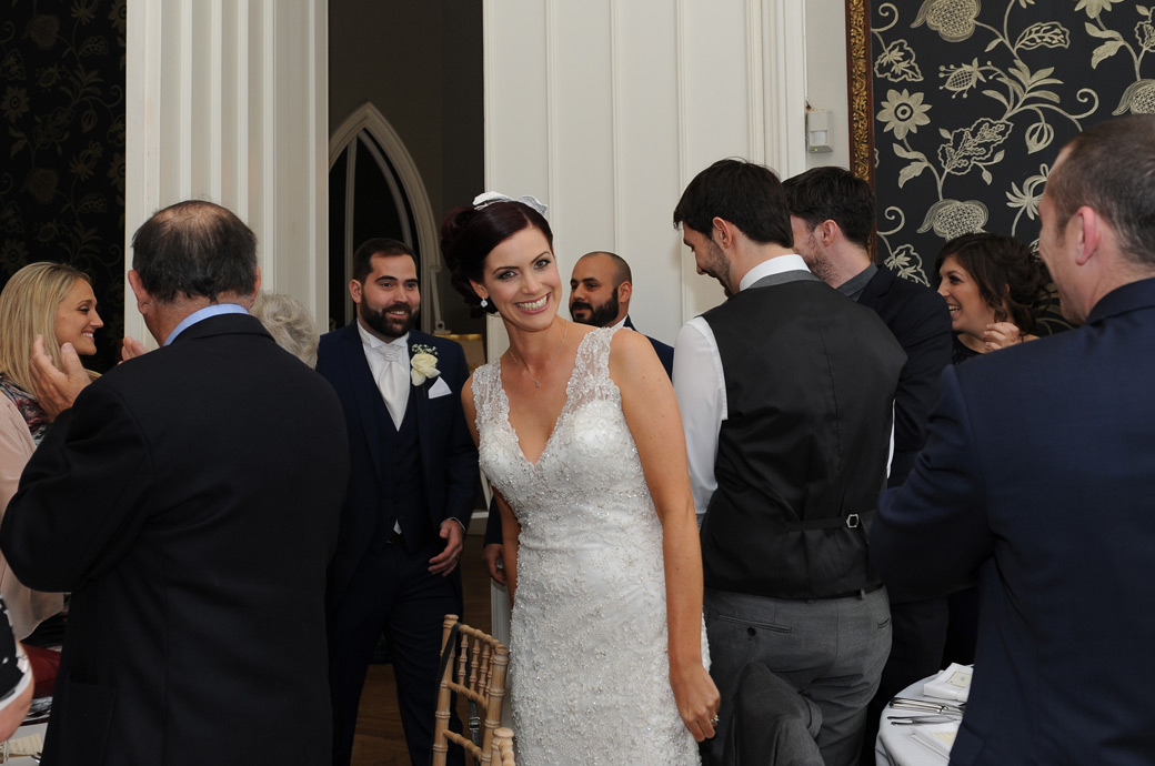 Smiling Bride and Groom enter the Orchid Room to the applause of the guests for their wedding breakfast at Nonsuch Mansion a popular wedding venue in Surrey