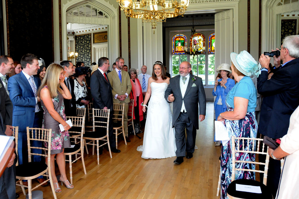 A proud Father and and excited Bride walk down the aisle in this wedding photograph taken at Nonsuch Mansion captured by Surrey Lane wedding photography