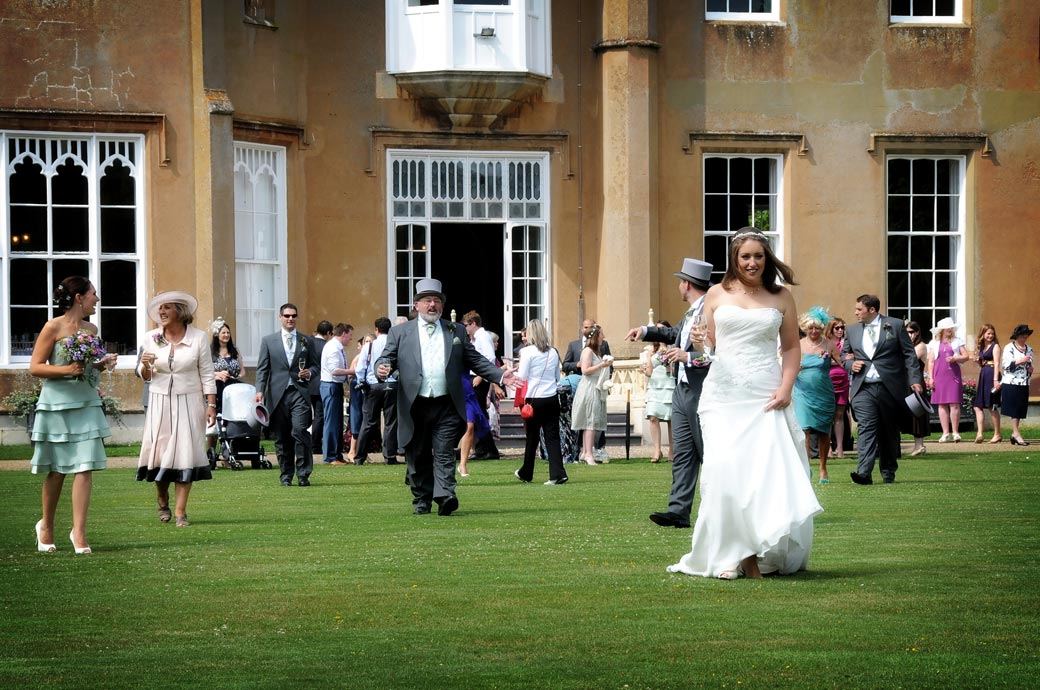An excited Bride leads the way across the lawn in this wedding picture taken at the lovely Nonsuch Mansion a Surrey wedding venue with a rich history