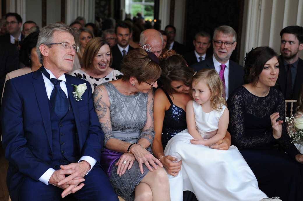 Cuddles and smiles for the cute little flower girl in the front row of the Orchid Room at the historic wedding venue Nonsuch Mansion in leafy Cheam Surrey