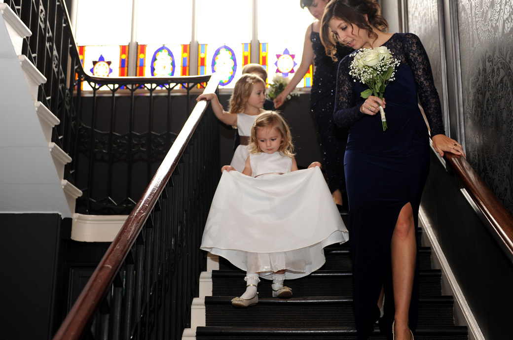Cute flower girls walking down the stairs with the bridesmaids in this lovely sweet wedding photograph taken at Nonsuch Mansion in Cheam by a Surrey Lane wedding photographer