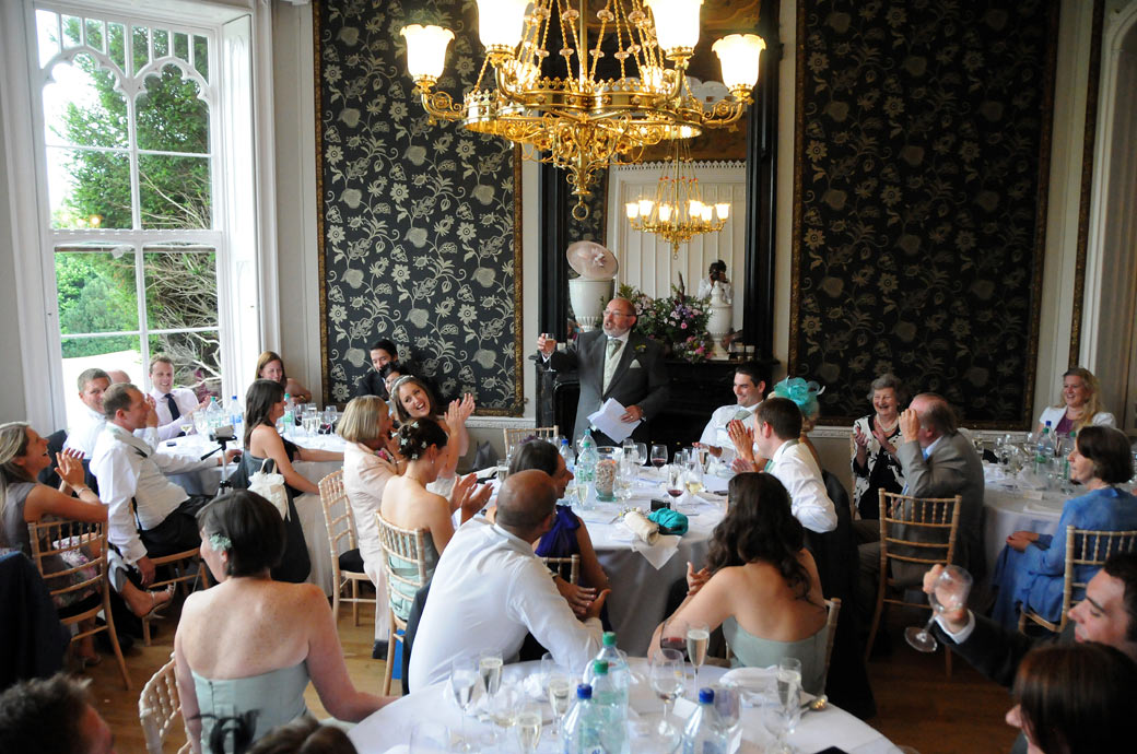 Applause and laughter in the Orchid Room at Surrey wedding venue Nonsuch Mansion as the father of the bride entertains the guests during the wedding breakfast speeches