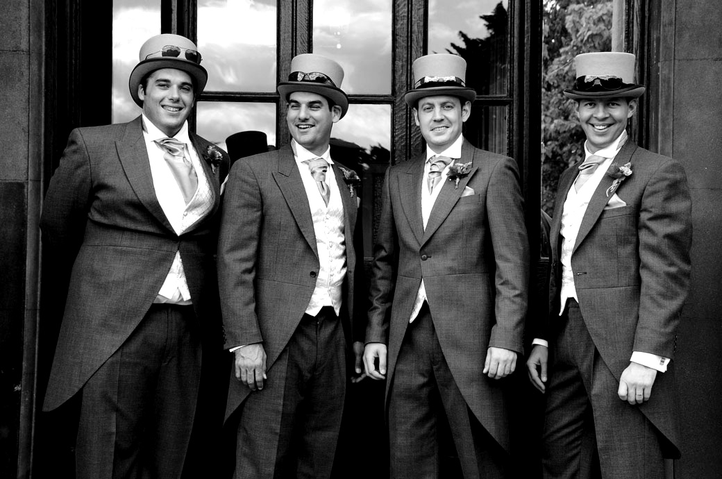 Smiling gents with their sunglasses on their top hats in this funny wedding photograph taken at Nonsuch Mansion by Surrey Lane wedding photographer