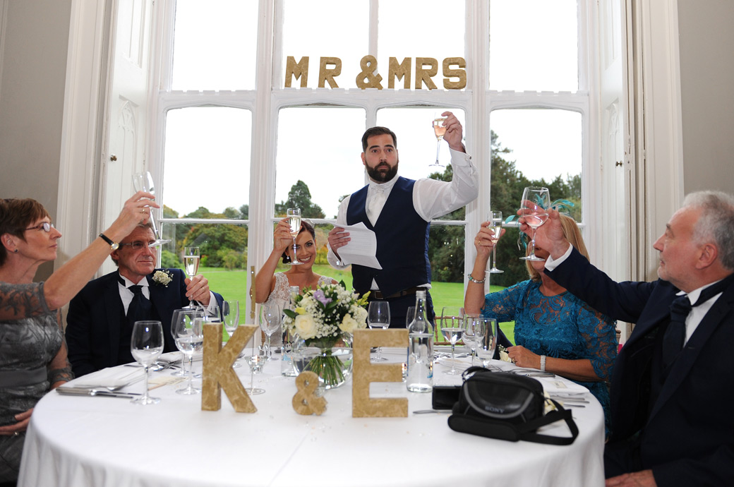 Groom raises a glass for a final toast during the wedding speeches in the Tulip Room at Nonsuch Mansion in Cheam captured by a Surrey Lane wedding photographer