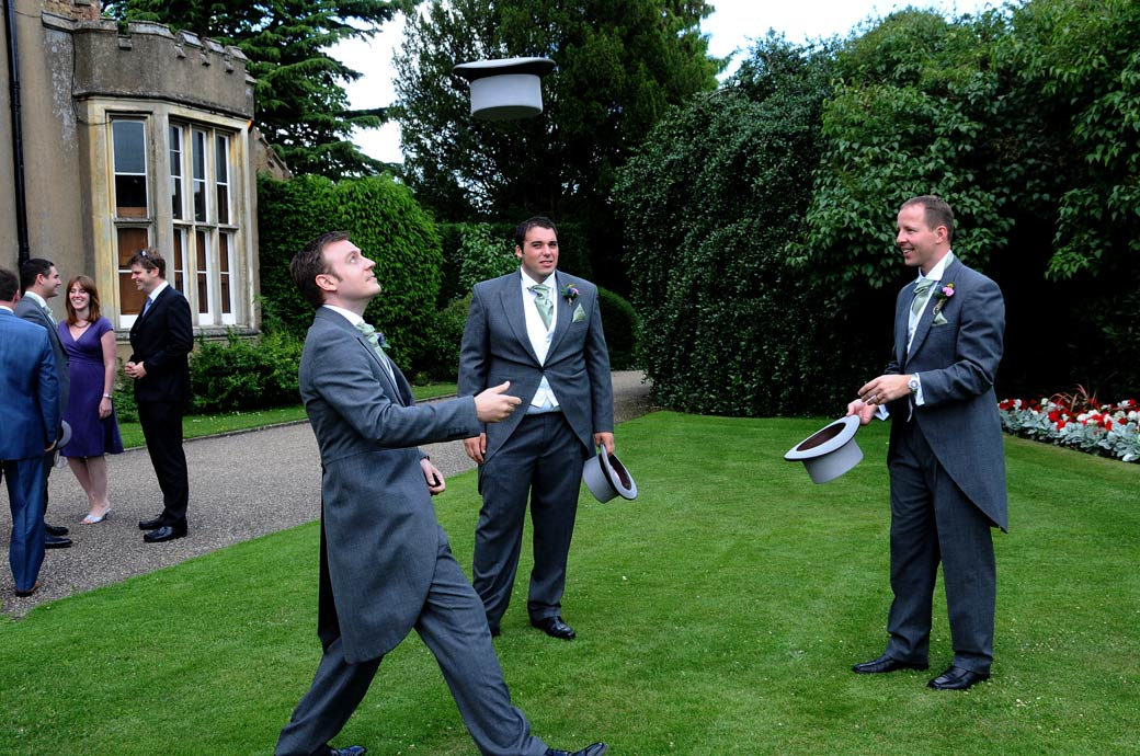 Wedding photo of the groomsmen playing around as they try to catch the top hats on the heads out on the lawn at Nonsuch Mansion a wedding venue in Surrey