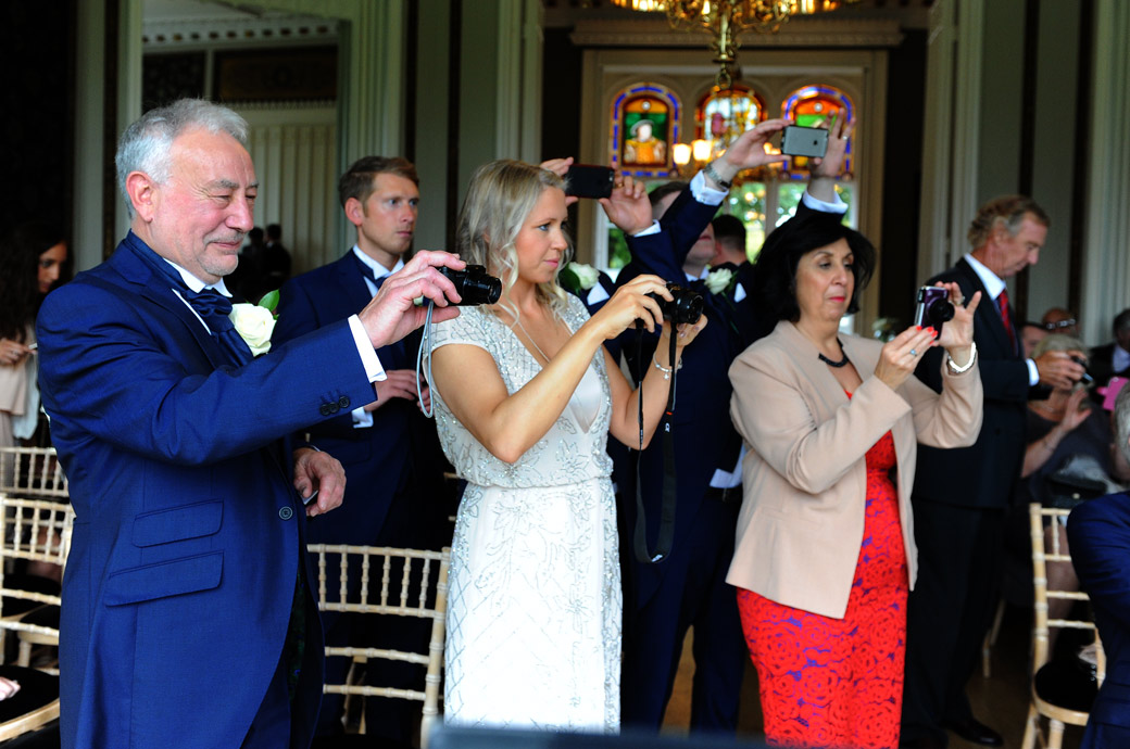 Family and guests all lining up their cameras to catch the happy couple in this post wedding photo taken in  the Orchid Room at the pleasant Nonsuch Mansion in Cheam Surrey